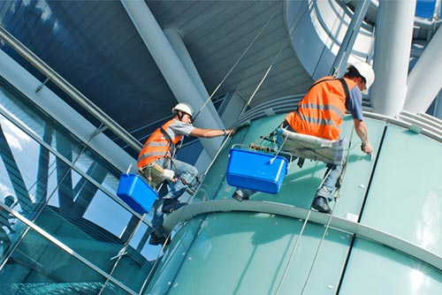 two men cleaning windows on a high rise building suspended with cables wearing orange high vis vests