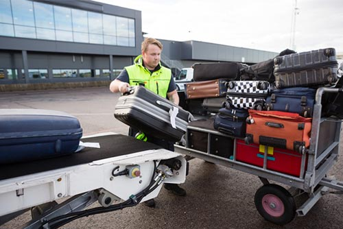 baggage handler in a fluorescent vest moving bags from an aeroplane on a trailer