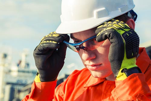 Man wearing ornage high visibility workwear with PPE