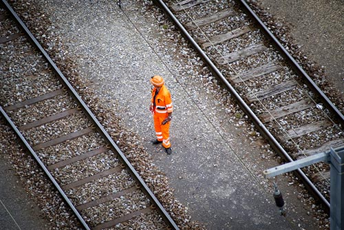 Rail worker in high visibility workwear standing working on the rail